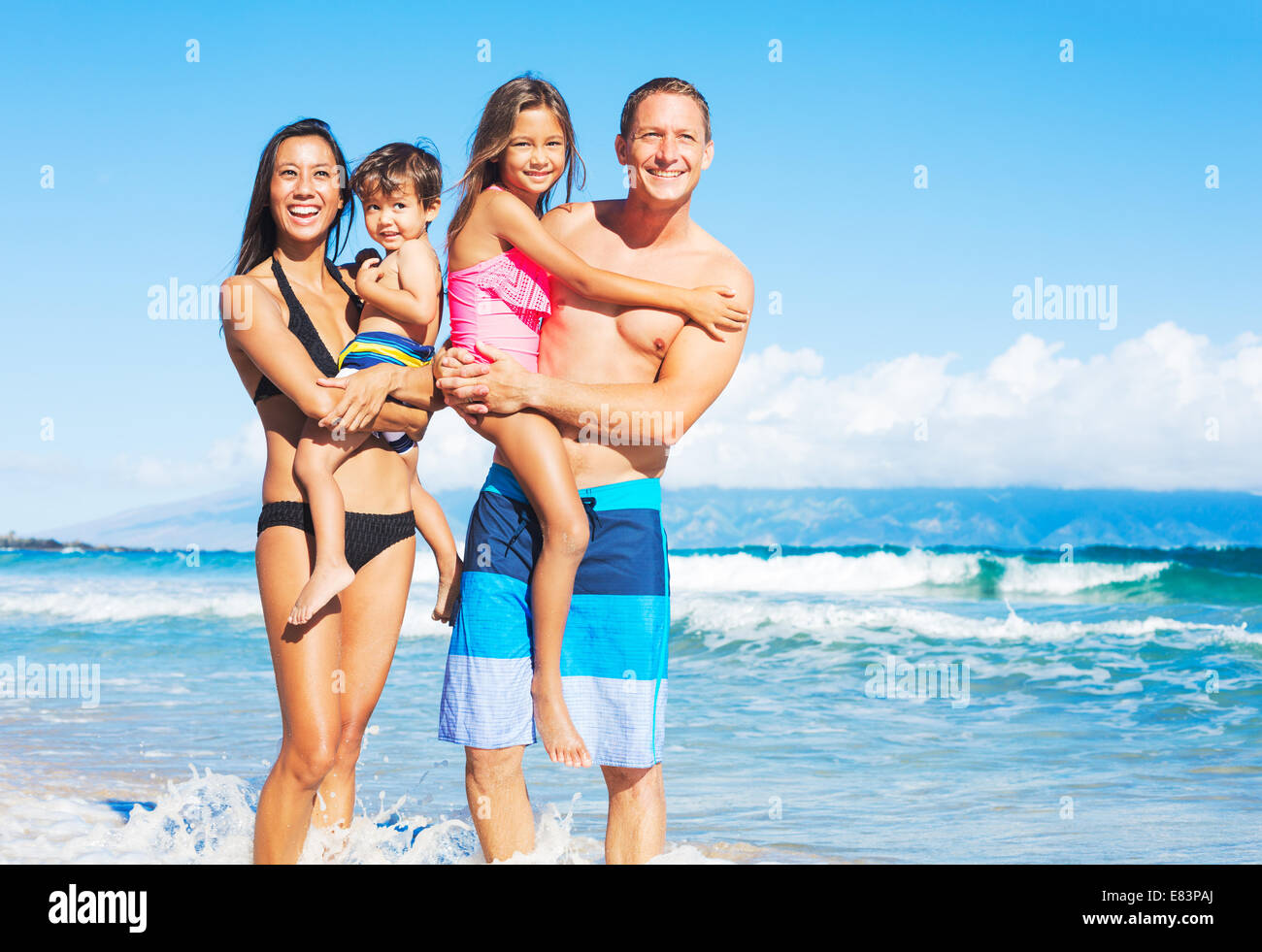 Happy Mixed Race Family of Four on Tropical Sunny Beach Stock Photo