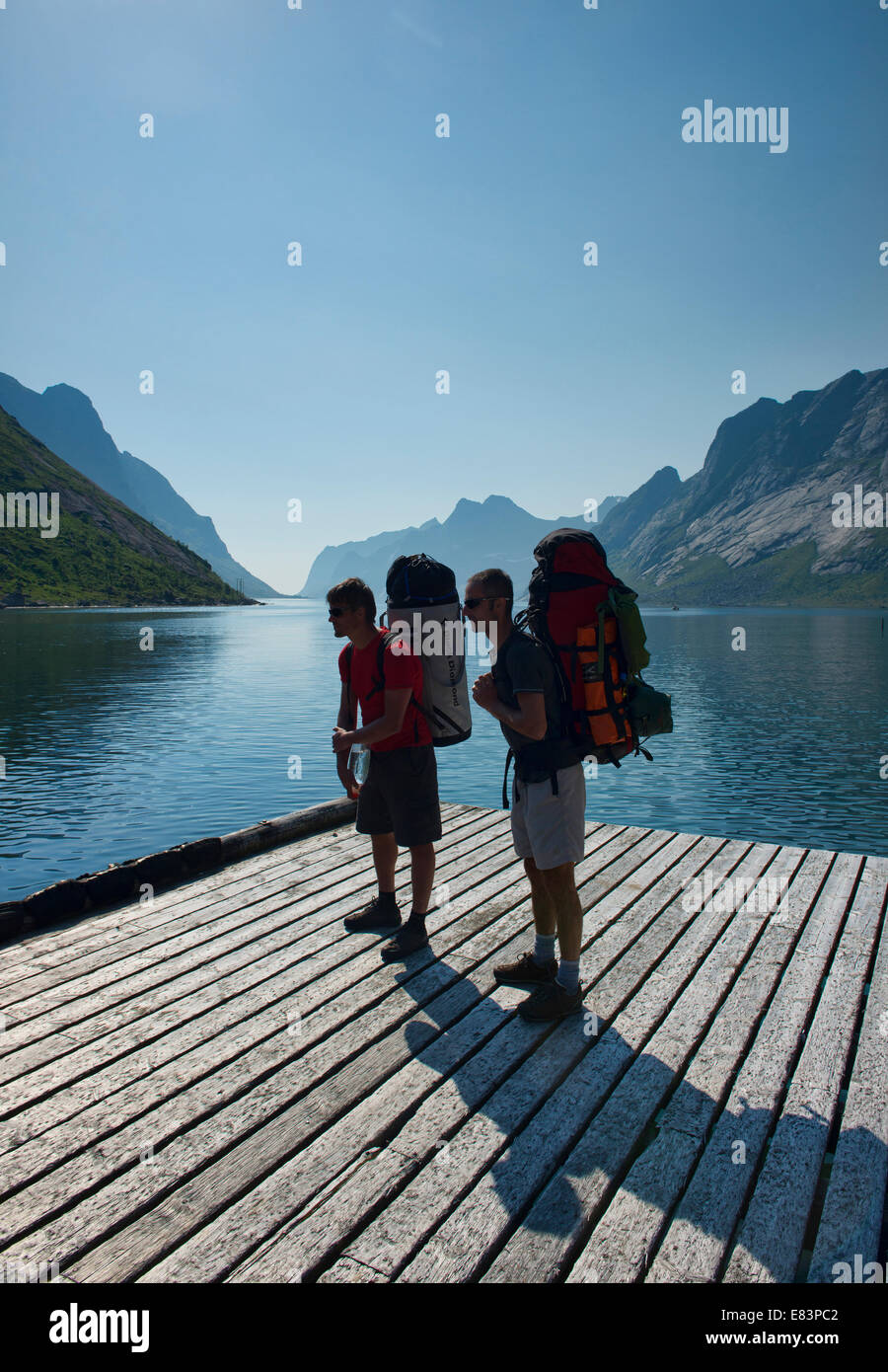 backpackers waiting for the ferry in the Lofoten Islands, Norway - Stock Image