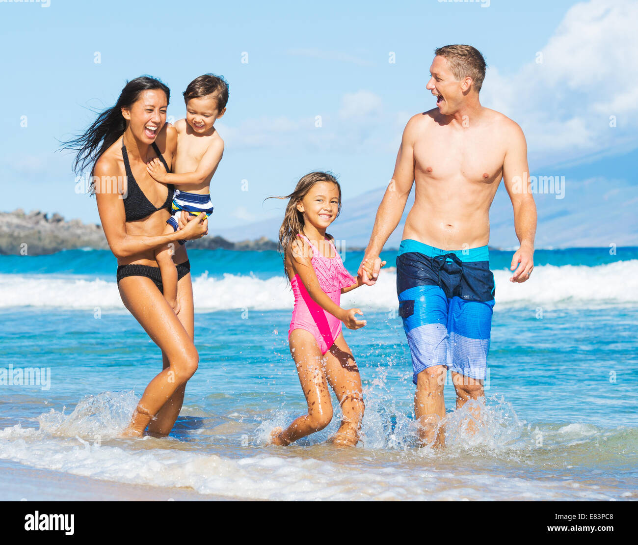 Happy Mixed Race Family of Four Playing and Having Fun on the Beach - Stock Image