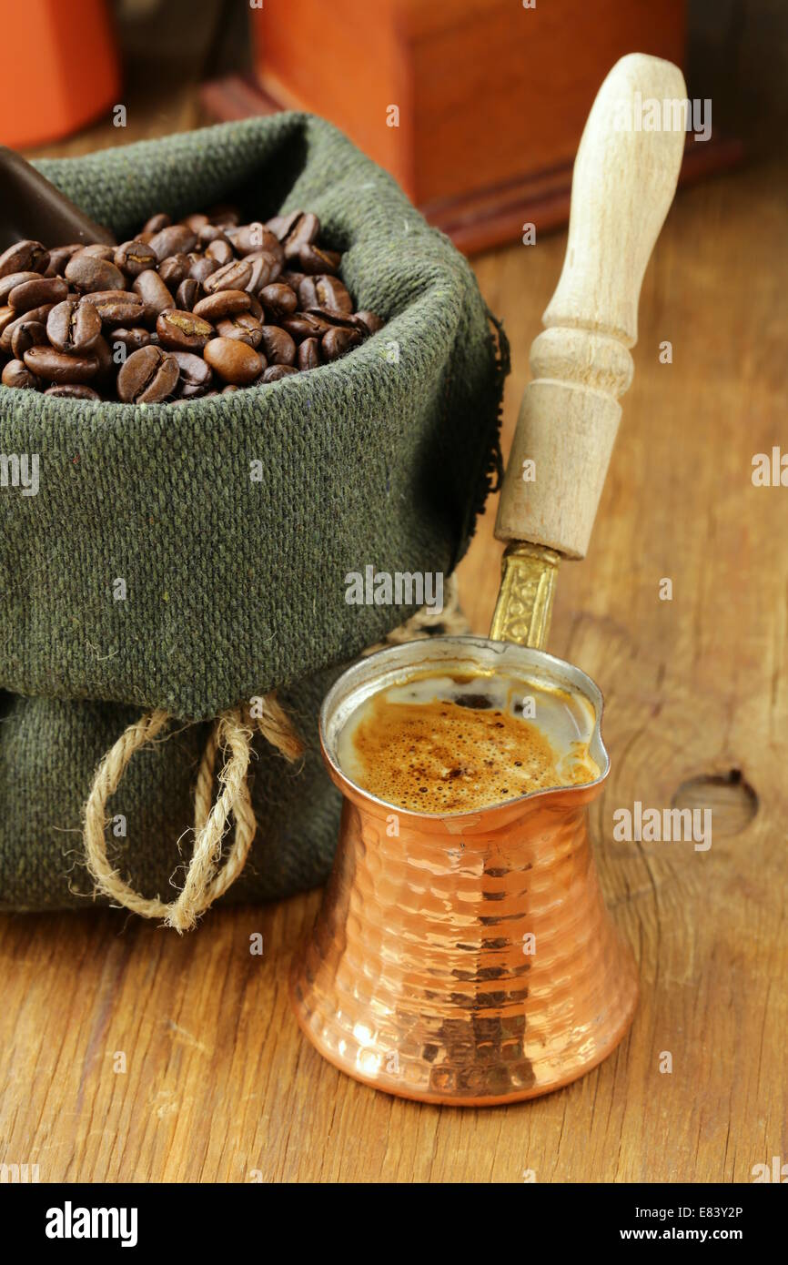 Still life coffee beans in a bag and copper coffee pot Stock Photo