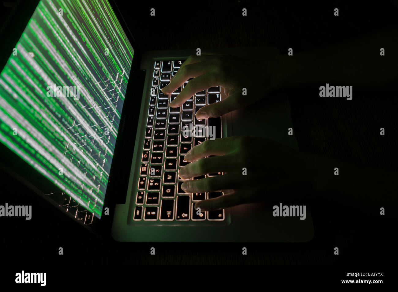 Computer hacker typing on keyboard with green matrix style graphics on the monitor - Stock Image
