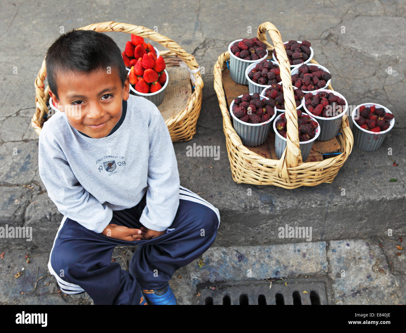Boy with fruit punnets sitting on the curb of a street, Ibarra grocery market, Imbabura Province, Ecuador - Stock Image