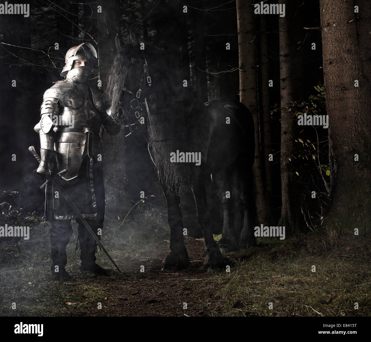Knight wearing armour standing beside his horse in the woods, Tyrol, Austria - Stock Image