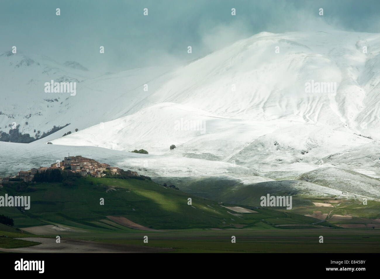 Castelluccio di Norcia and the Piano Grande in late spring, with snowy mountains; Monti Sibillini National Park, - Stock Image