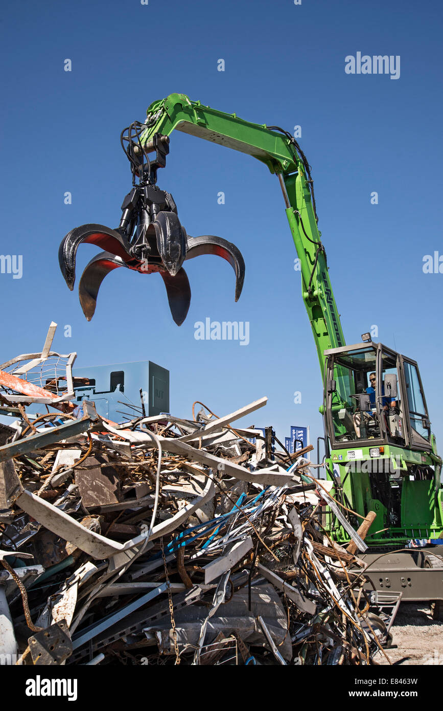 Heavy machine picks up after a mountain of scrap at the site of a recycling plant. - Stock Image
