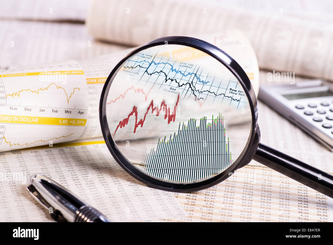 Lupe with stock prices on papers with rate table. - Stock Image