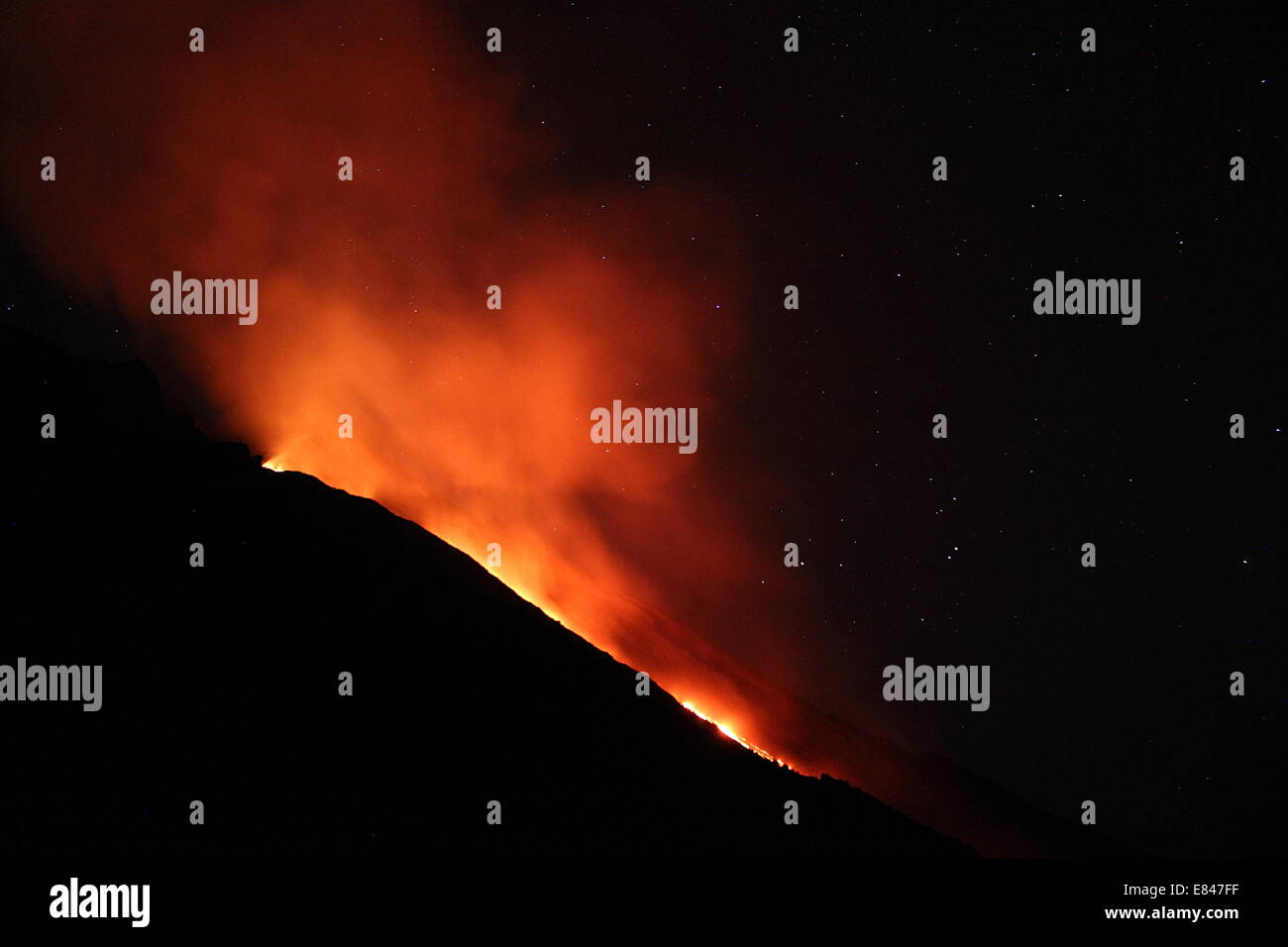 Lava pouring from the summit of Mount Stromboli in the Italian Aeolion Islands. - Stock Image