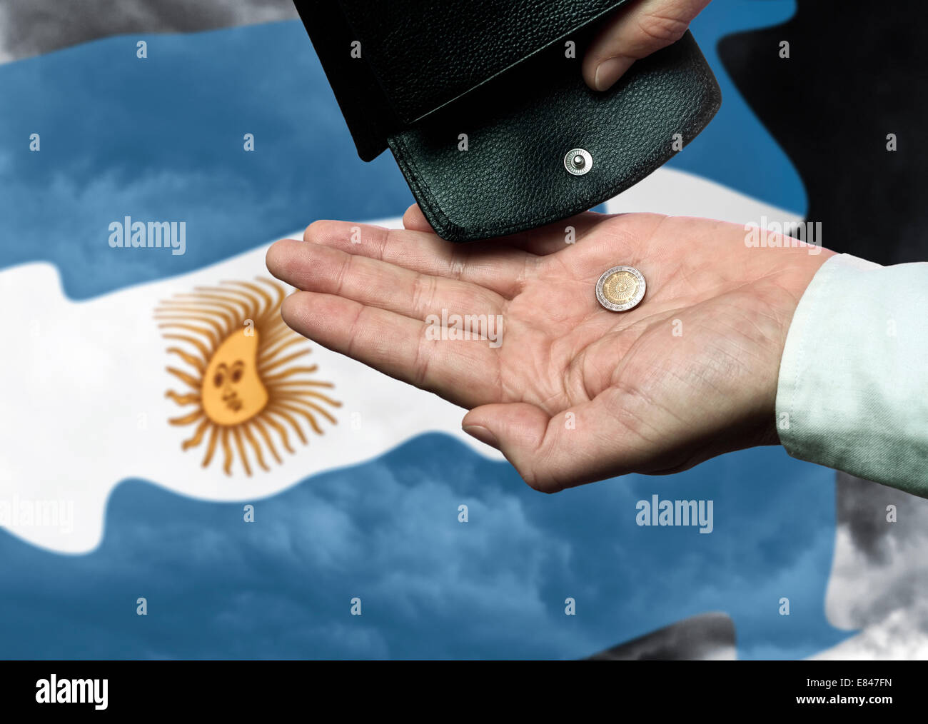 Hand with purse and Argentine peso in front of the flag as a symbol of the threat of national bankruptcy of the - Stock Image