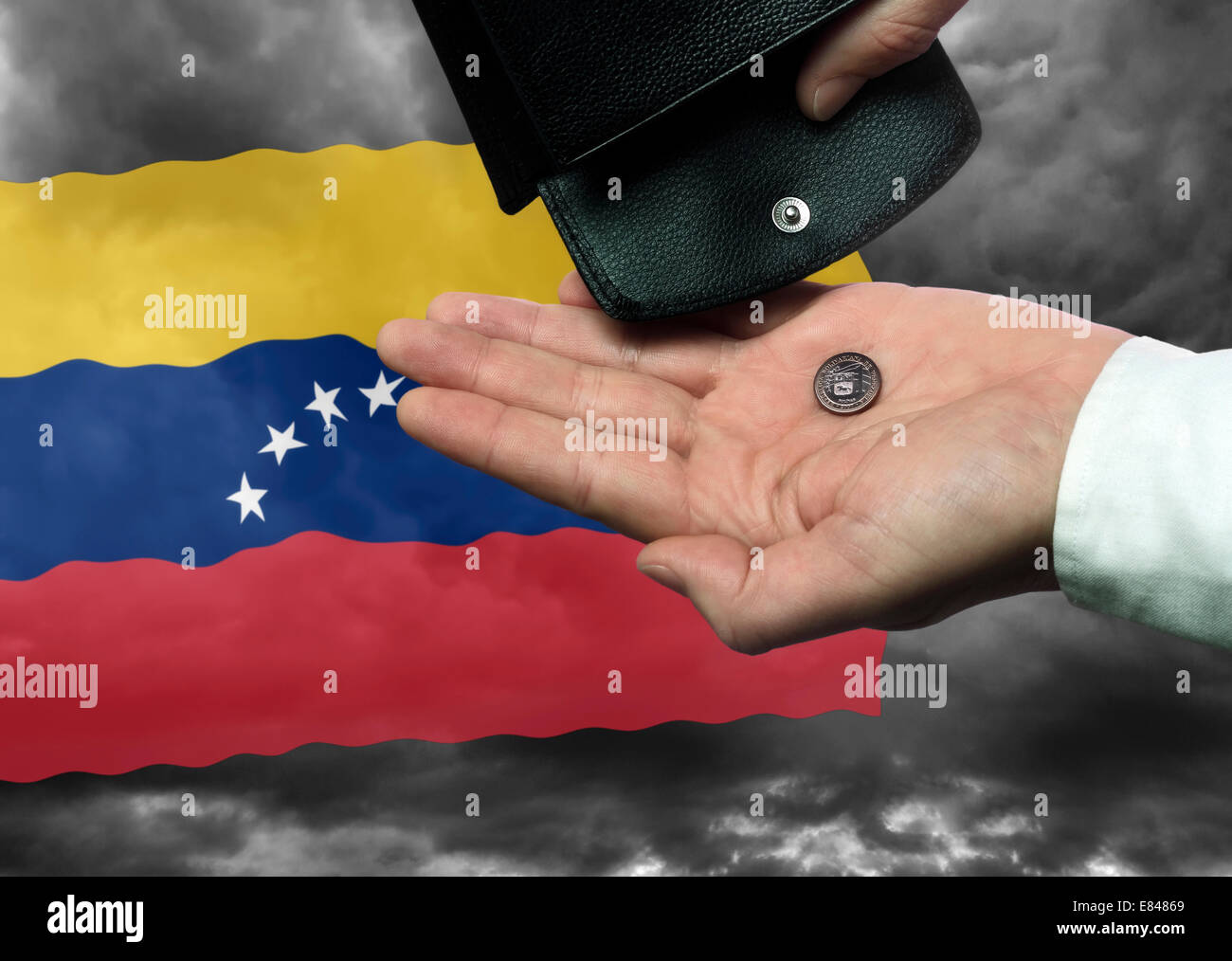 Hand with purse and Bolivar coin before the Venezuelan flag as a symbol of the threat of national bankruptcy of - Stock Image