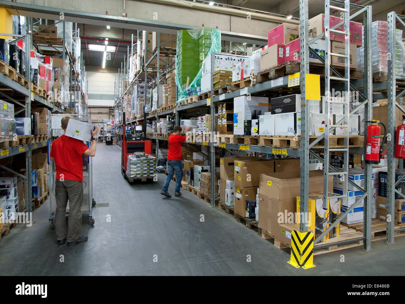 Two workers in a warehouse with high shelves. - Stock Image