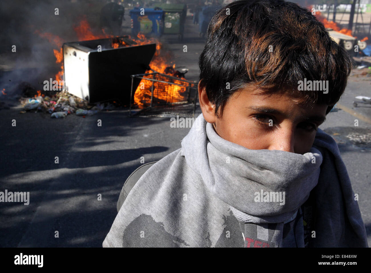 Athens. 30th Sep, 2014. A boy stands beside a burning barricade during a protest in Athens, Greece on Sept. 30, - Stock Image