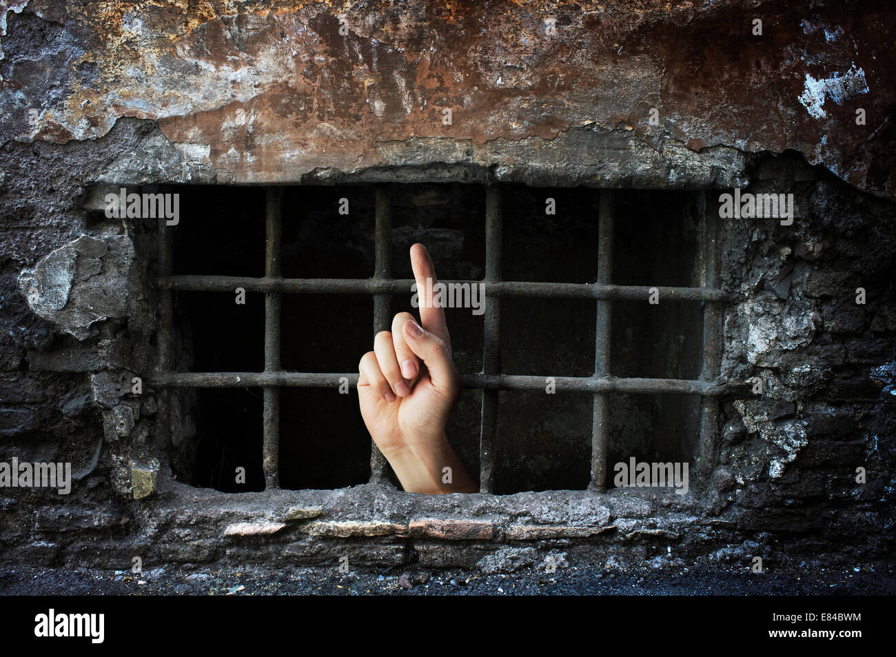 Conceptual image of a hand reaching out from a dungeon. - Stock Image