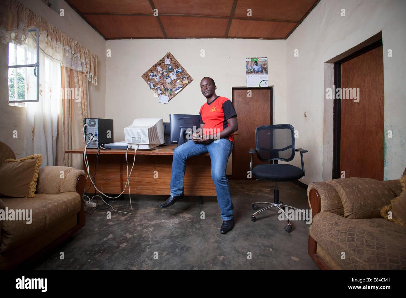 Rwandan website administrator running an online business from his home office, Kigali, Rwanda - Stock Image