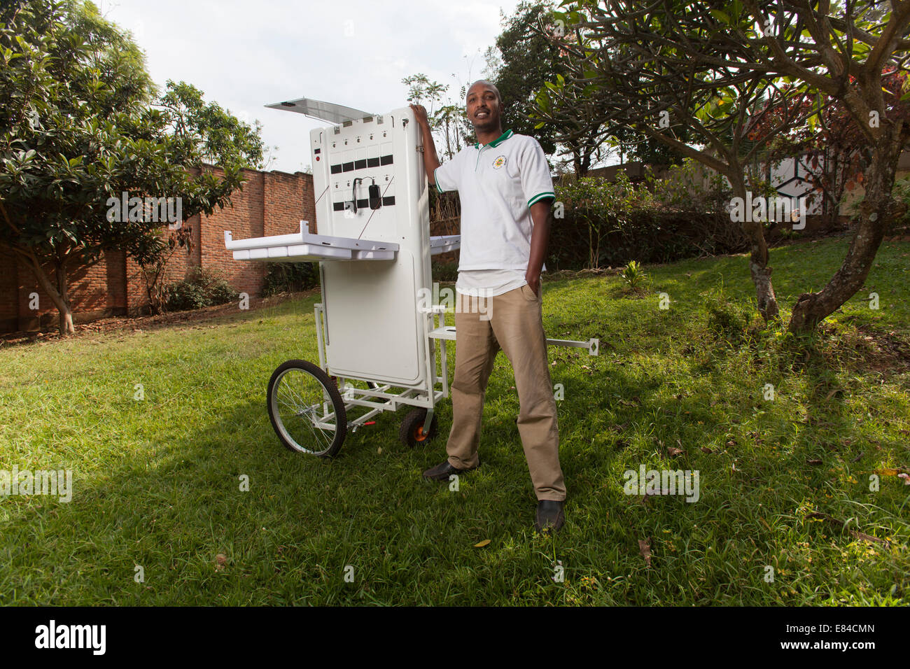 Solar energy entrepreneur posing with a portable booth designed to sell electricity in off-grid communities, Kigali, - Stock Image