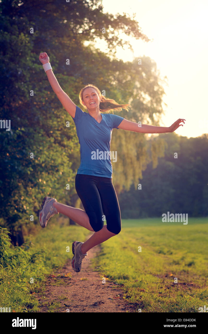 Energetic woman leaping in the air with a happy smile full of vitality as she runs along a country track during - Stock Image