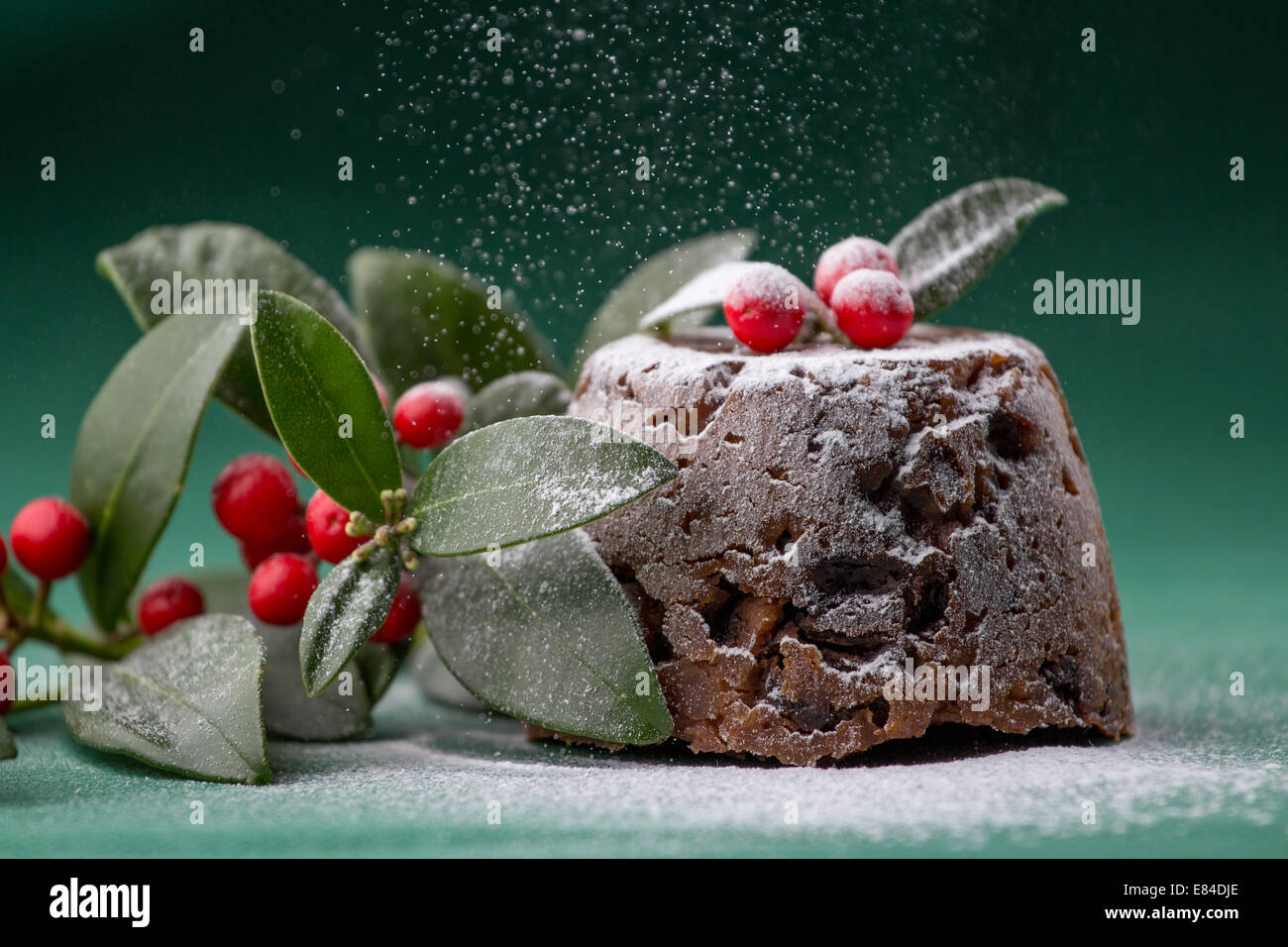 Christmas pudding dressed with winter berries and leaves and dusted with icing sugar - Stock Image