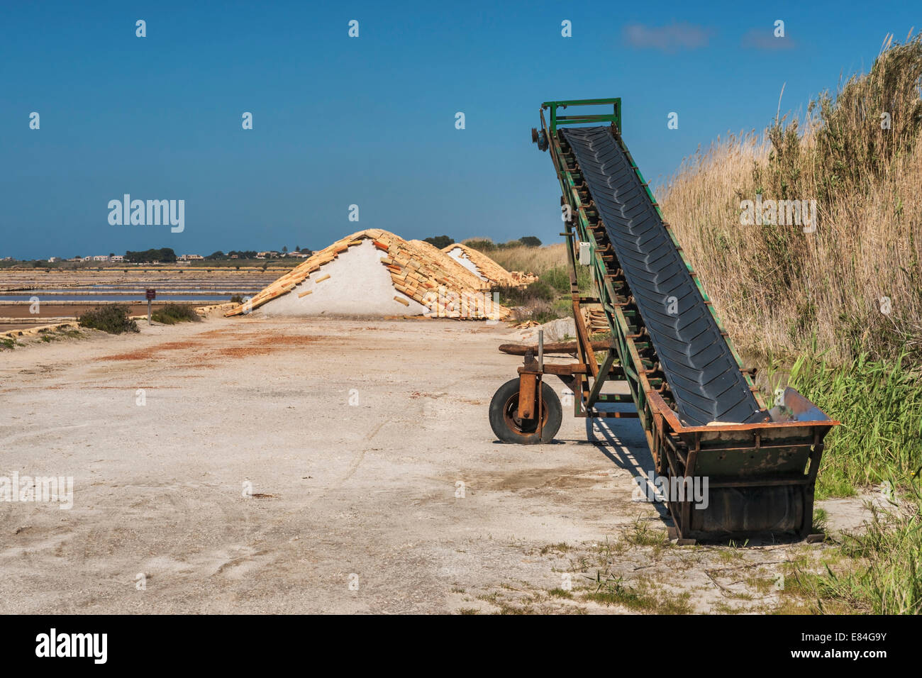Conveyor belt and salt hill in a saltern, Murana, Trapani, Sicily, Italy, Europe - Stock Image
