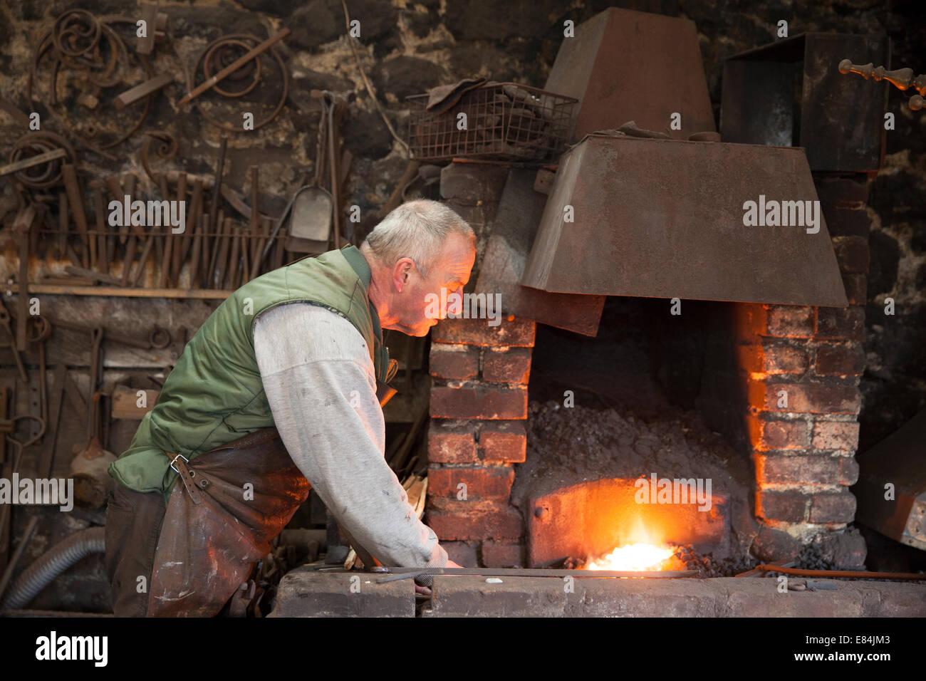 Traditional blacksmith at work in his forge, Moretonhampstead, Dartmoor, Devon - Stock Image