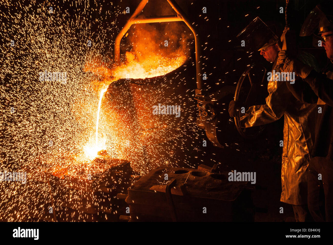 Molten high heat stainless steel is poured into into sand casting molds. - Stock Image