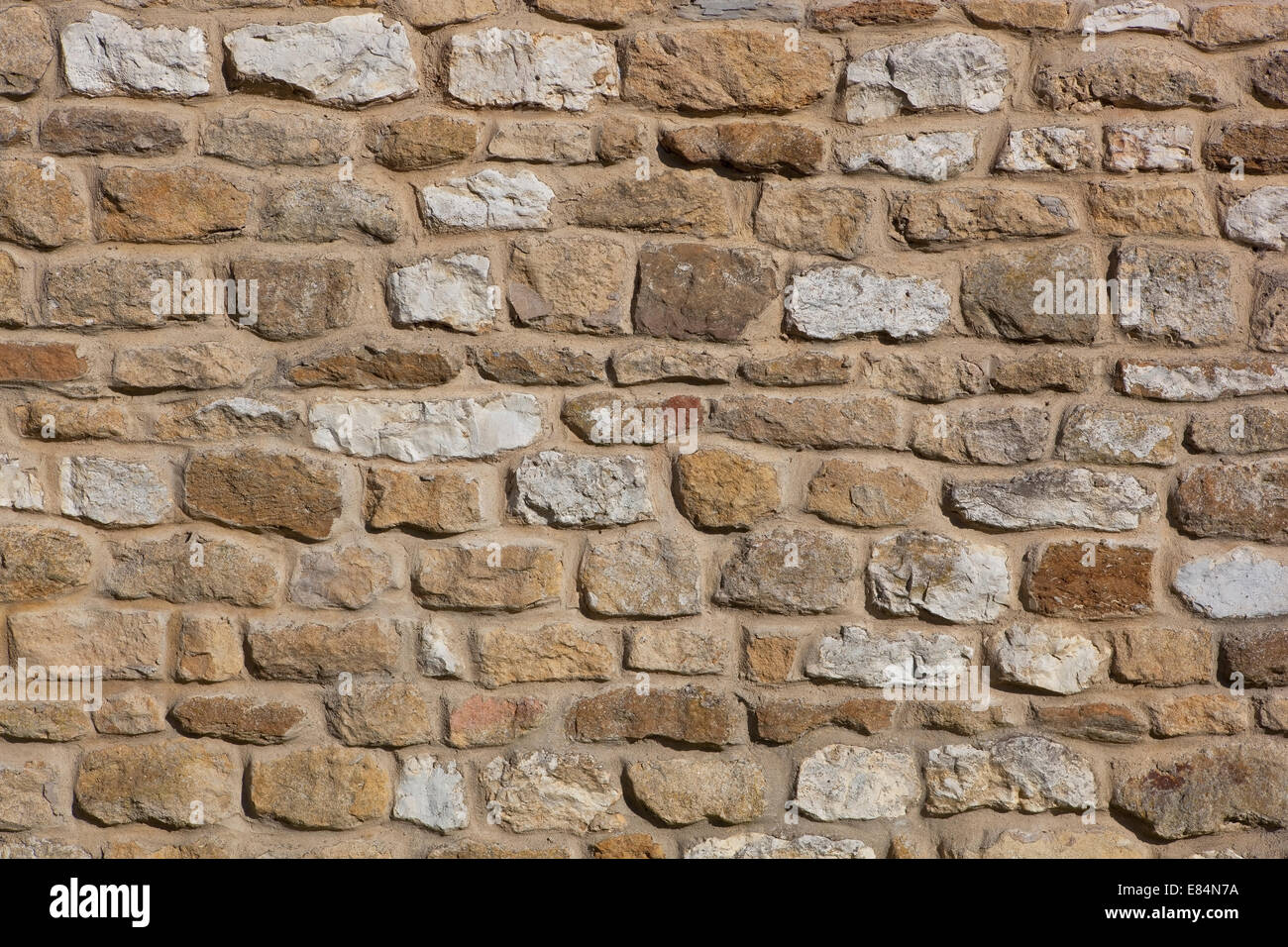 Architectural background pattern and textures of a natural stone wall bonded with mortar - Stock Image