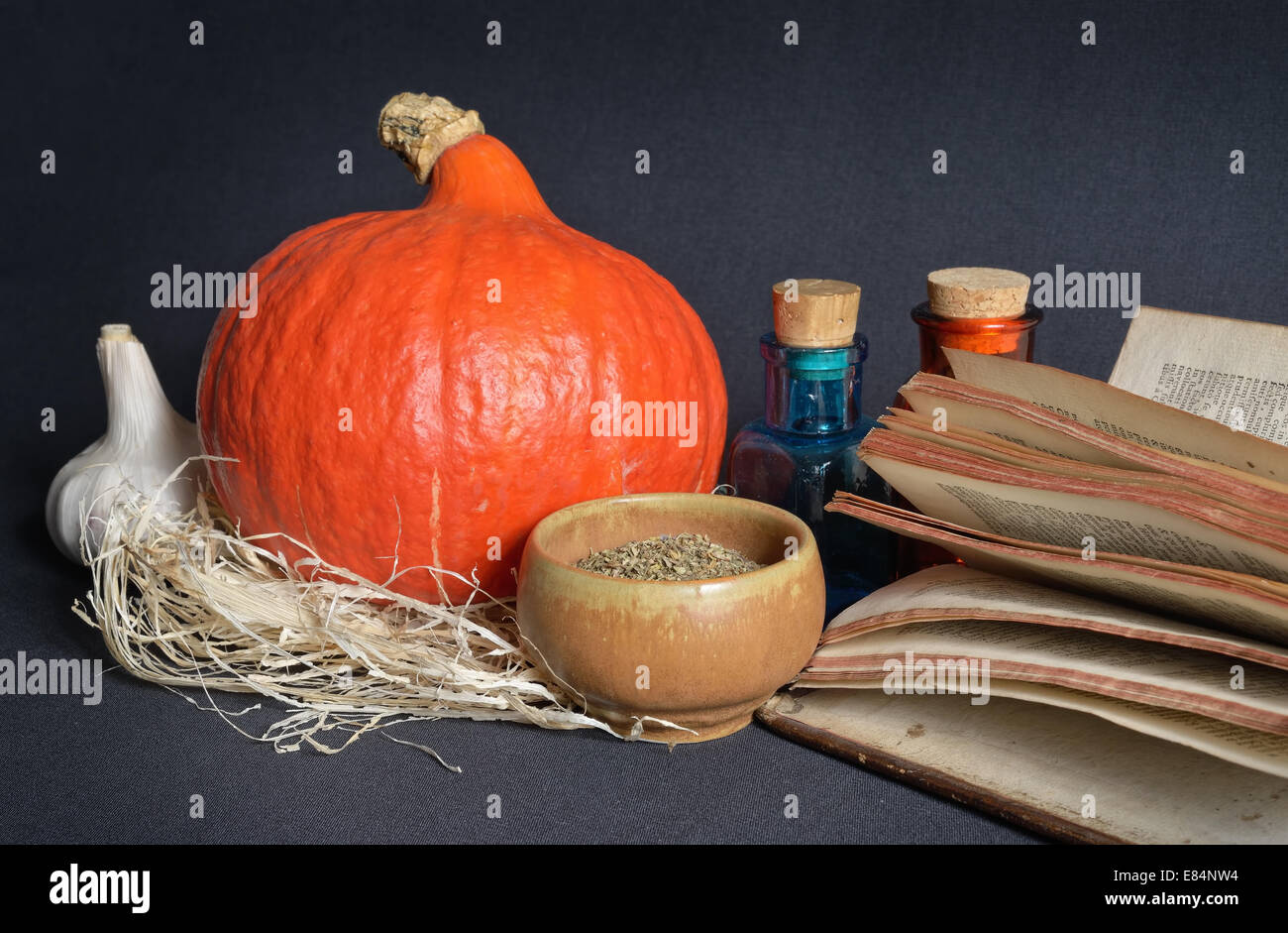 Herbs in ceramic cup, garlic, Halloween pumpkin, antique pharmacy glass and book on dark background - Stock Image
