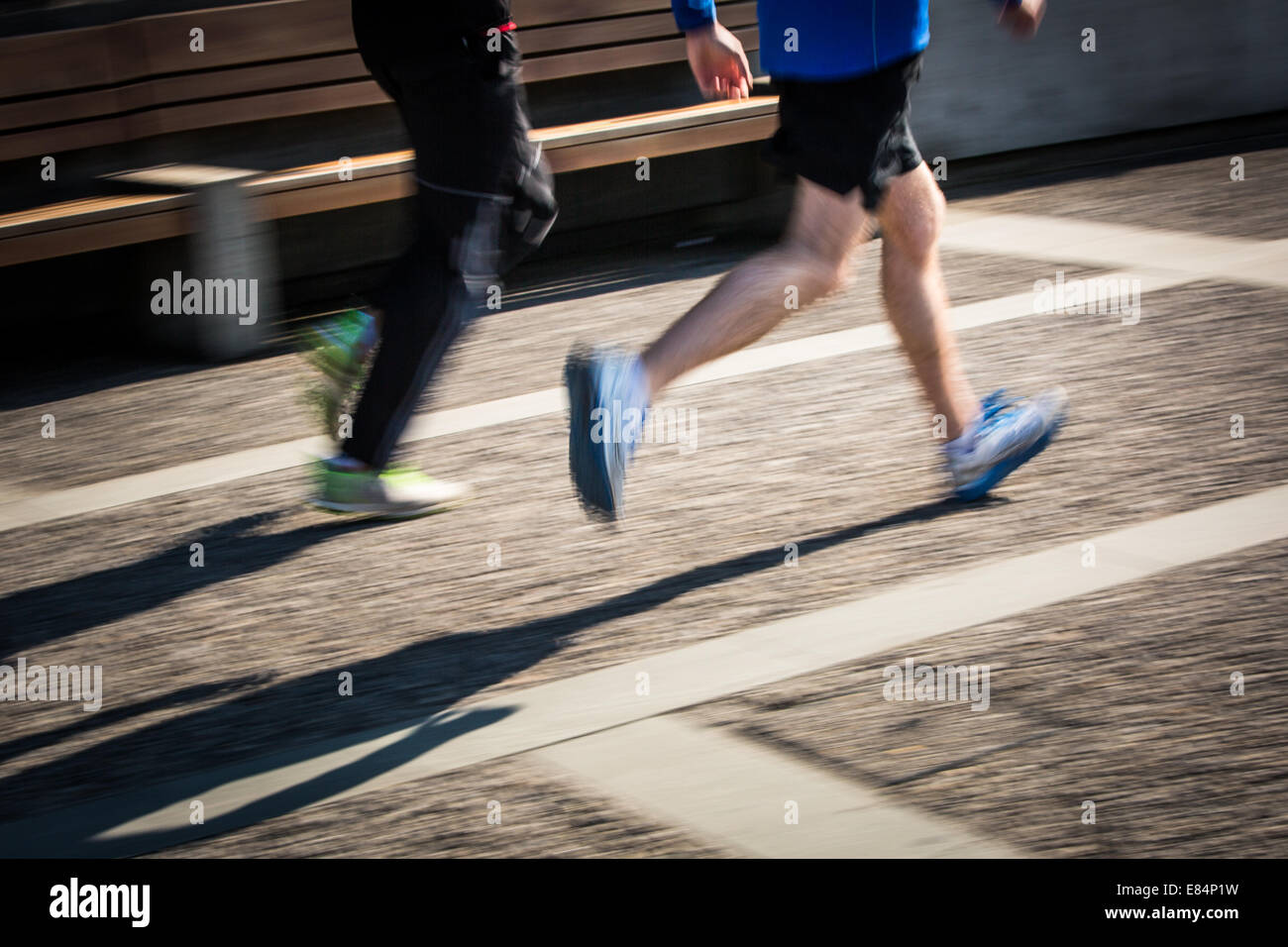 Motion blurred runner's feet in a city environment (panning technique used - motion blurred image; color toned - Stock Image