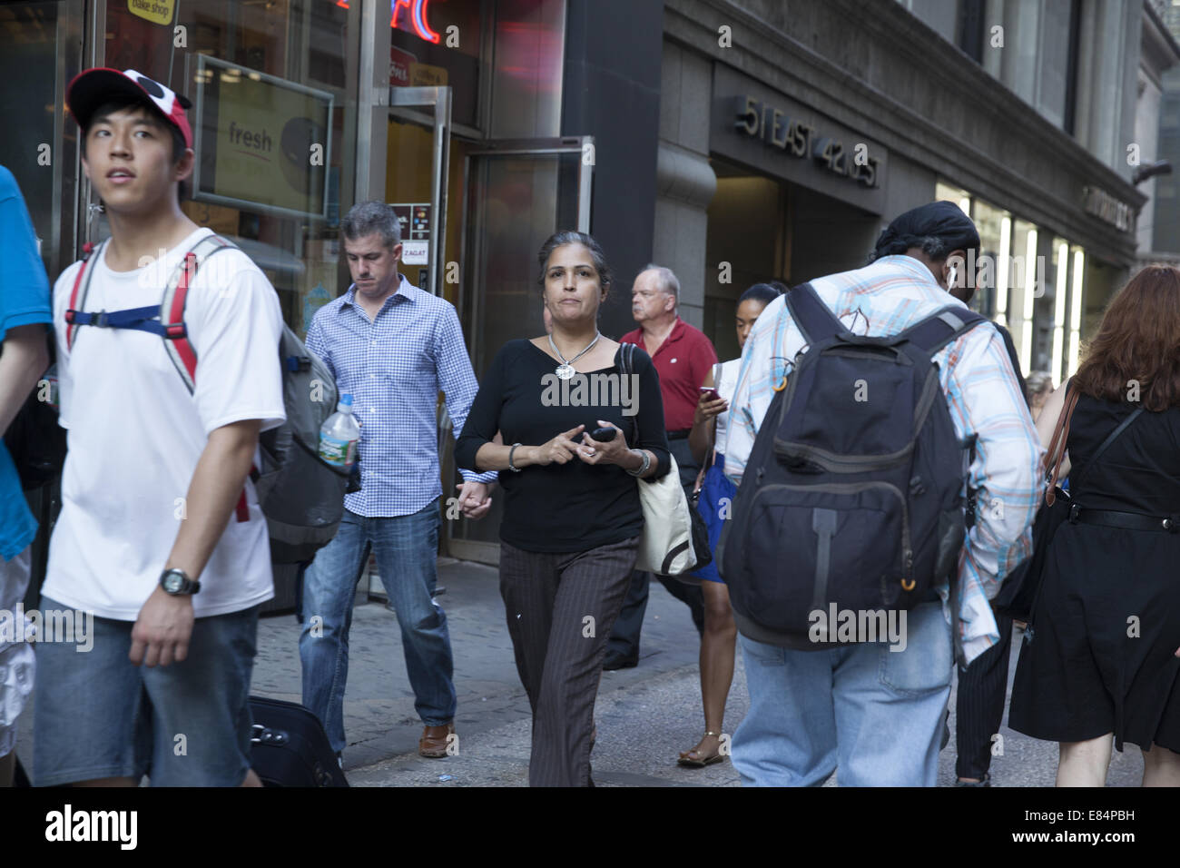 People walk along E. 42nd St.in Manhattan, NYC. - Stock Image