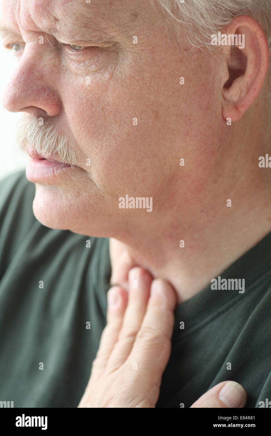Senior man experiences difficulty breathing. - Stock Image