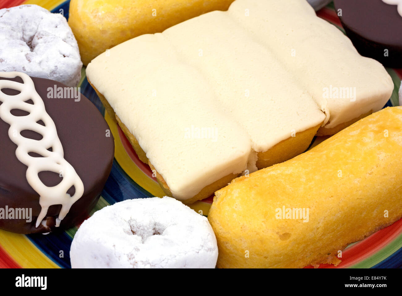 A very close view of junk food including powdered donuts, cream filled cakes, chocolate iced cakes and iced covered - Stock Image