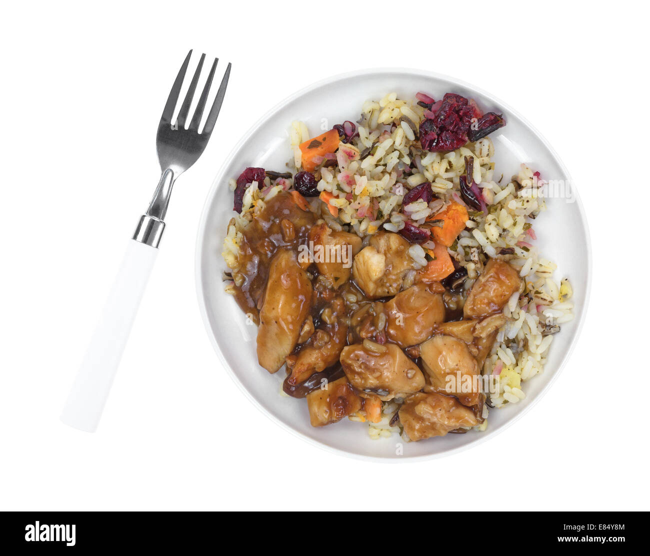 Top view of a cooked TV dinner with chicken in a pecan sauce, rice and cranberries in a small plate with fork to - Stock Image