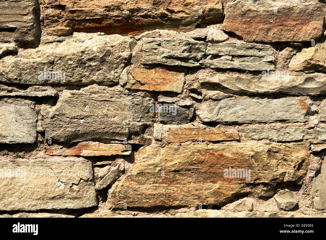 Old wall of reddish stones - Stock Image