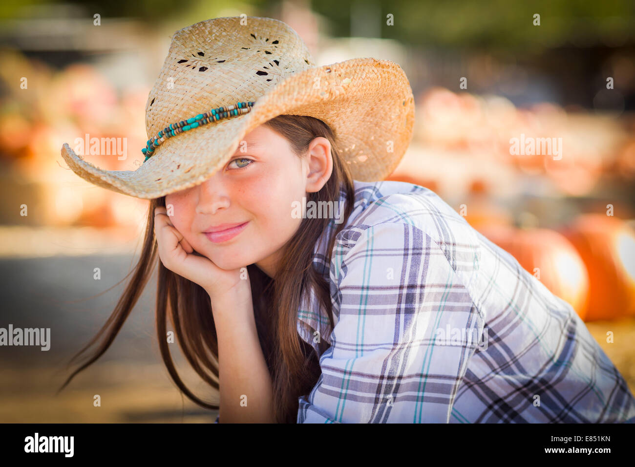 Pretty Preteen Girl Wearing Cowboy Hat Portrait at the Pumpkin Patch in a Rustic Setting. - Stock Image