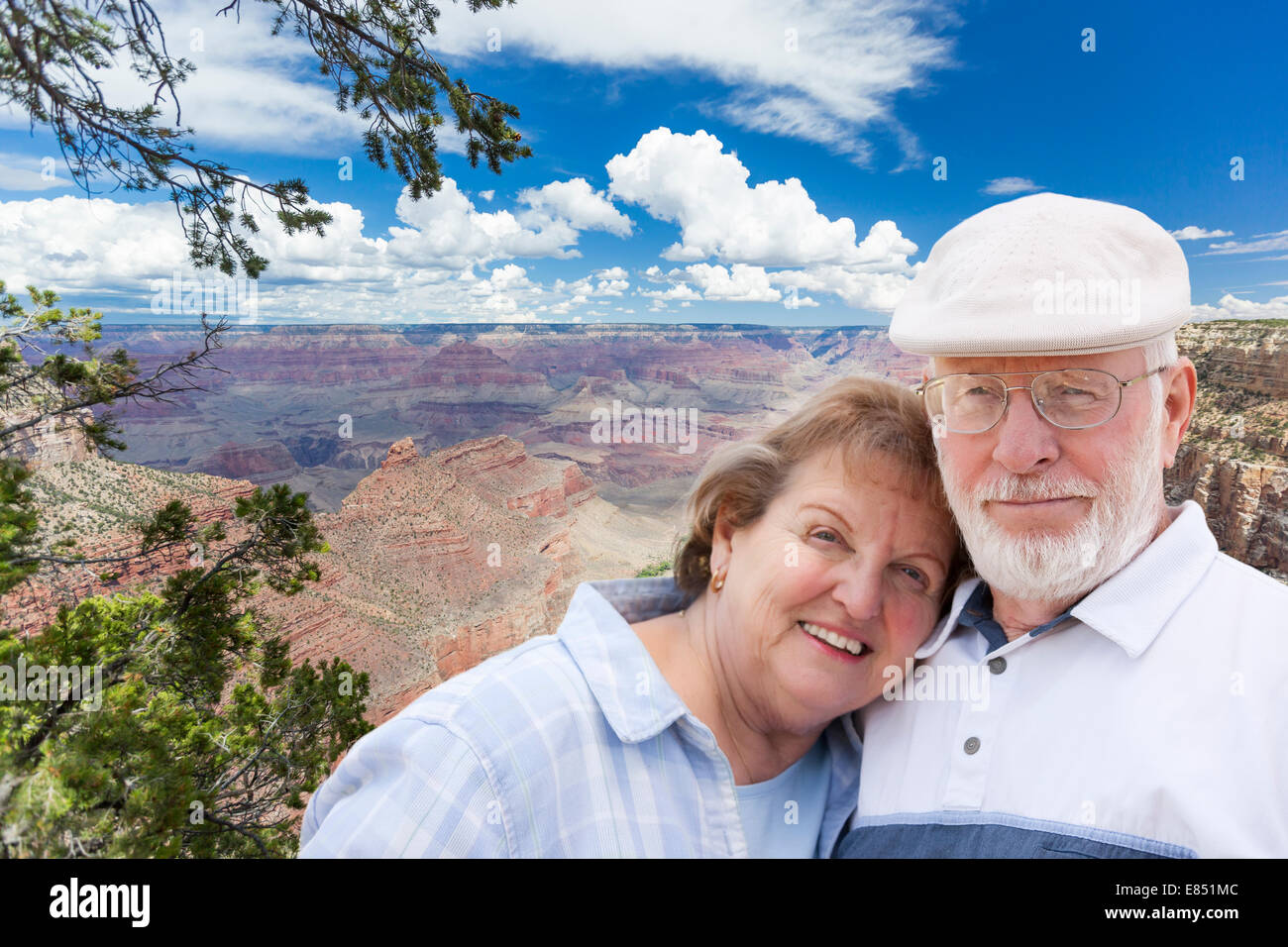 Happy, Hugging Senior Couple Posing on the Edge of The Grand Canyon. - Stock Image