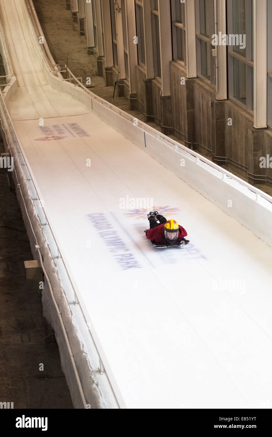 Skeleton athlete sliding on track in the Ice House, a year-round training facility for  athletes to practice push - Stock Image