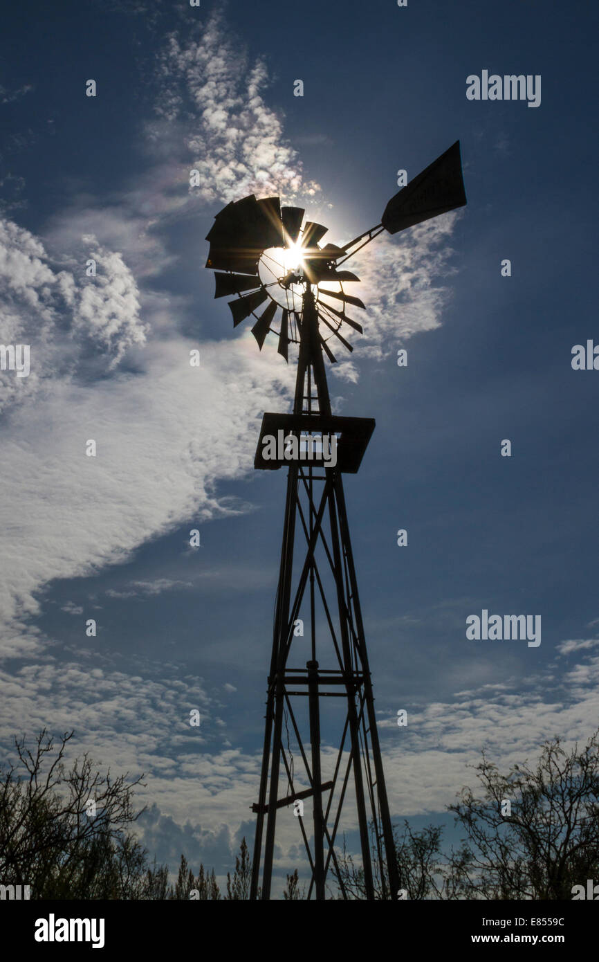Silhouette of Windmill with starburst at Dugout Wells in Big Bend National Park. - Stock Image