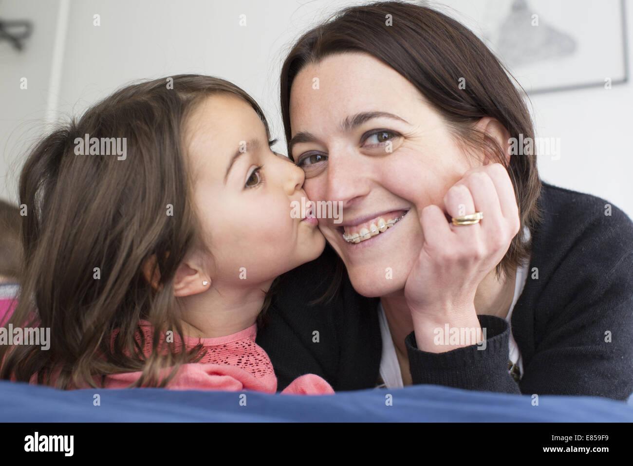 Little girl kissing mother's cheek - Stock Image