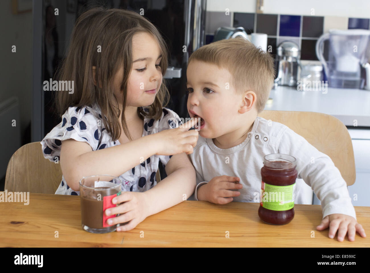 Young siblings tasting contents of jars with their fingers - Stock Image