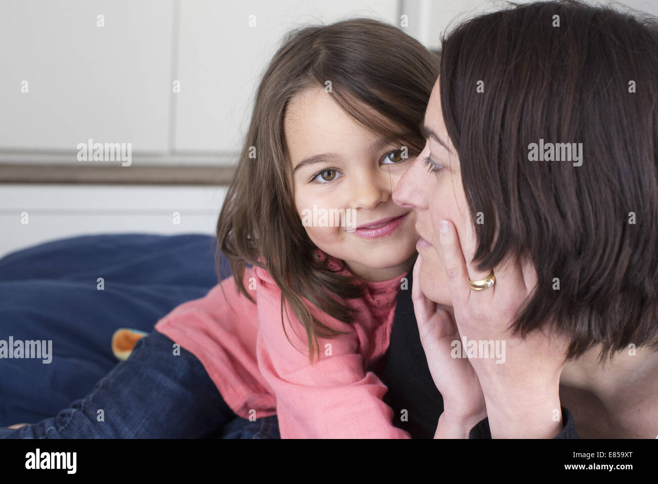 Little girl embracing her mother and smiling - Stock Image