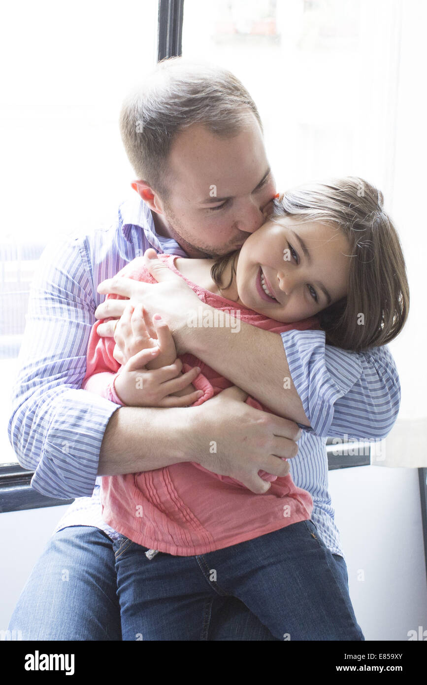 Father holding daughter on his lap, kissing her cheek - Stock Image