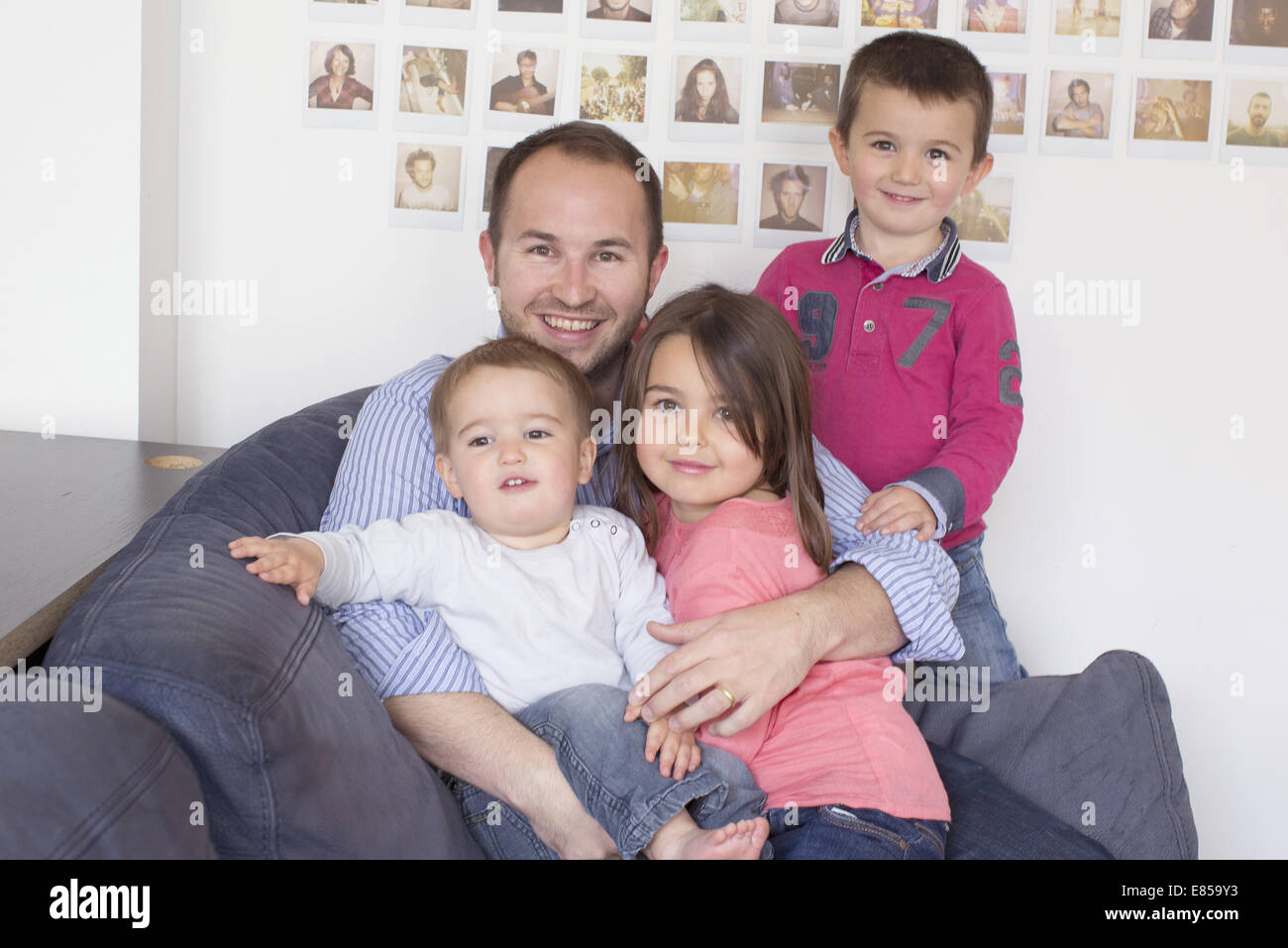 Father and children sitting together on sofa, portrait - Stock Image