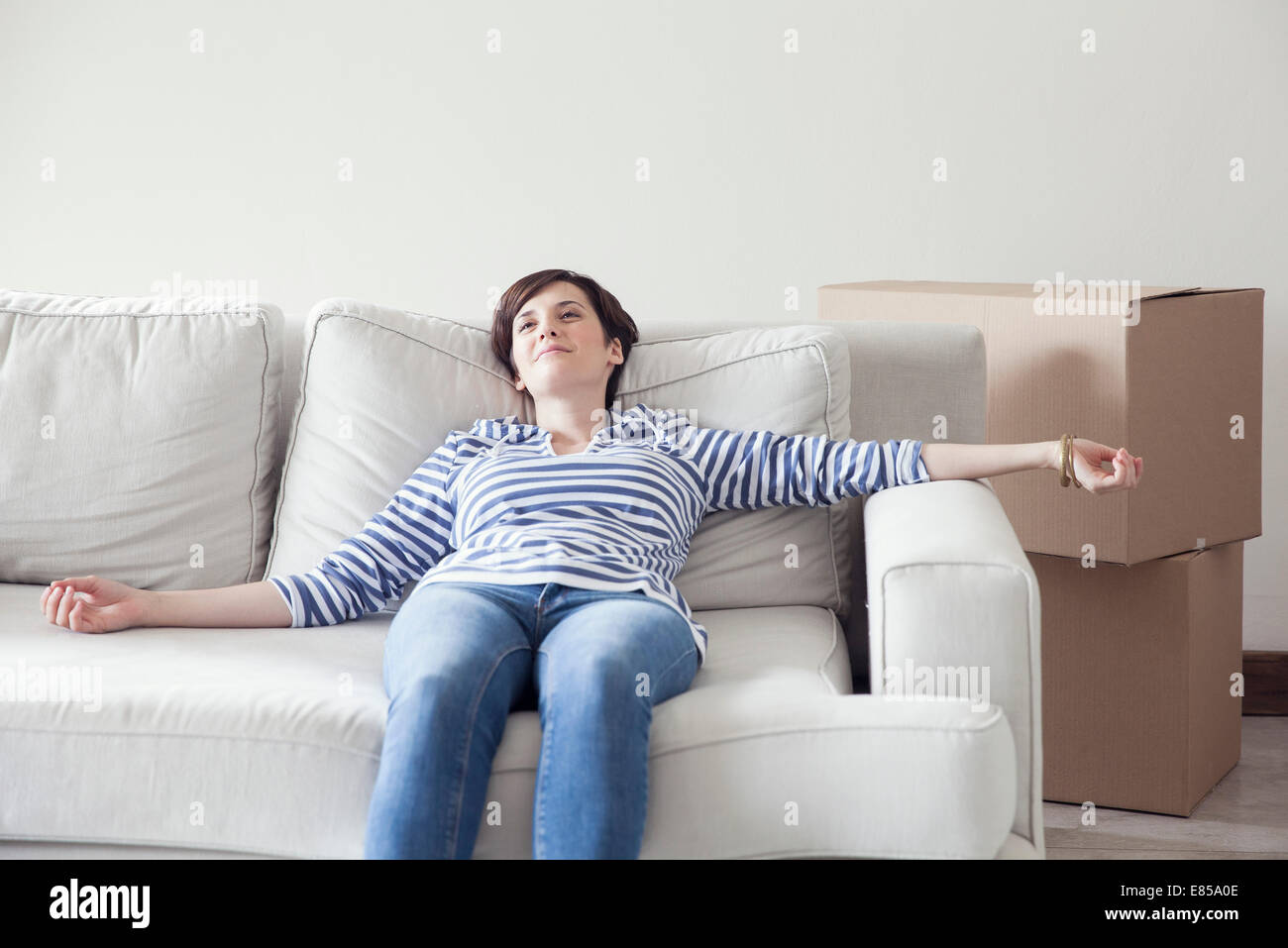 Woman resting on sofa while moving house - Stock Image
