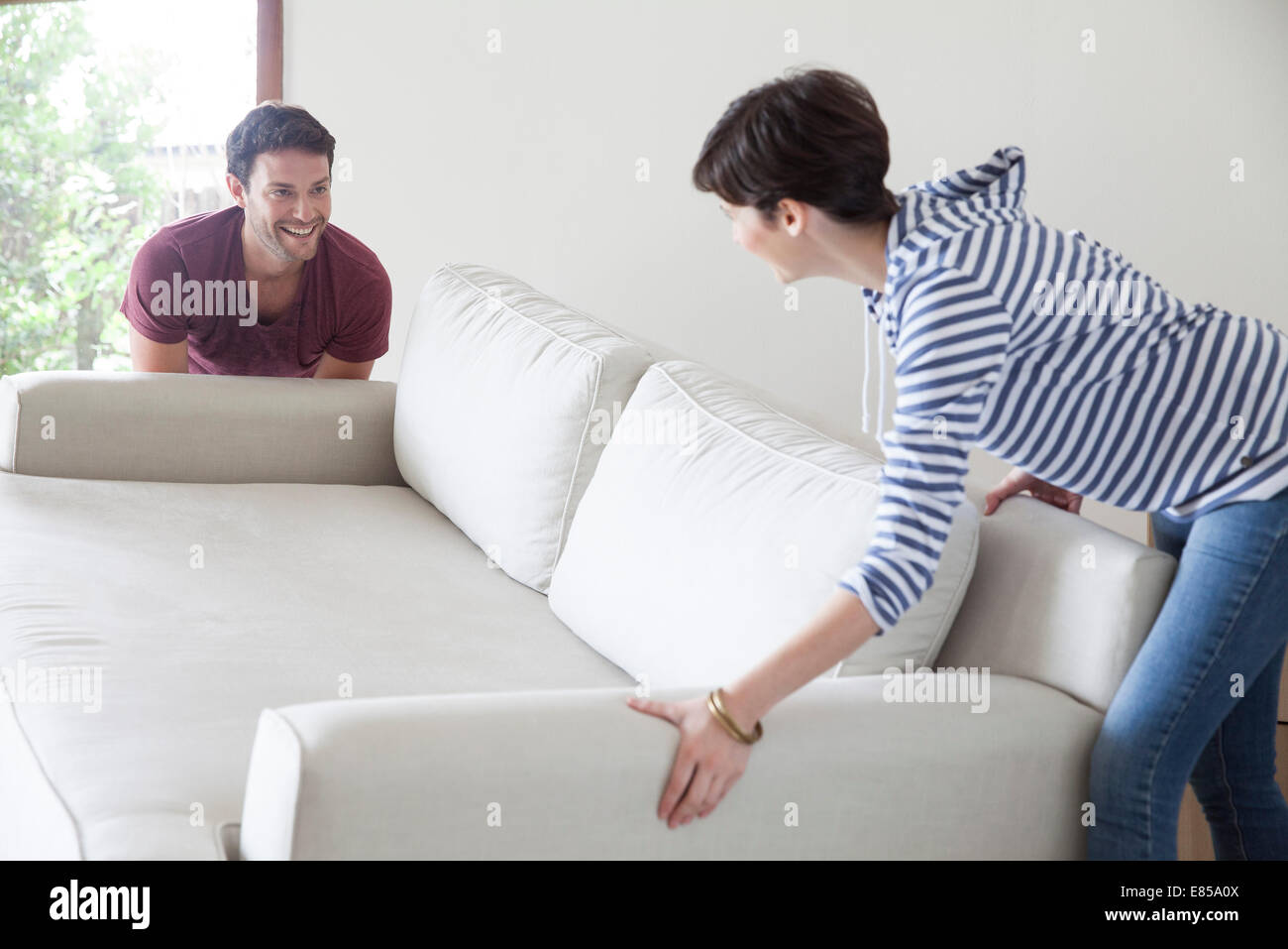 Couple moving sofa together - Stock Image