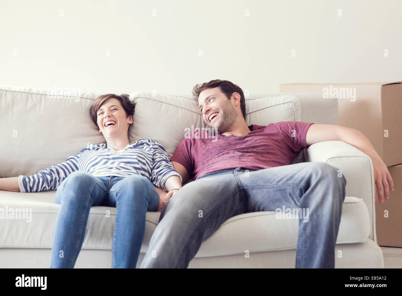 Couple relaxing on sofa while moving house - Stock Image