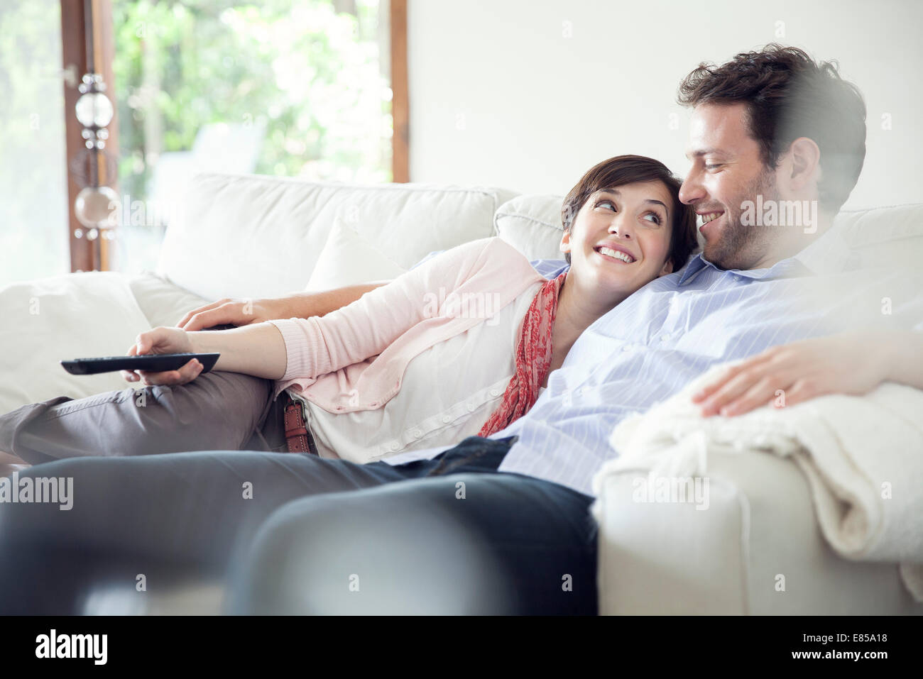 Couple watching TV together on sofa - Stock Image