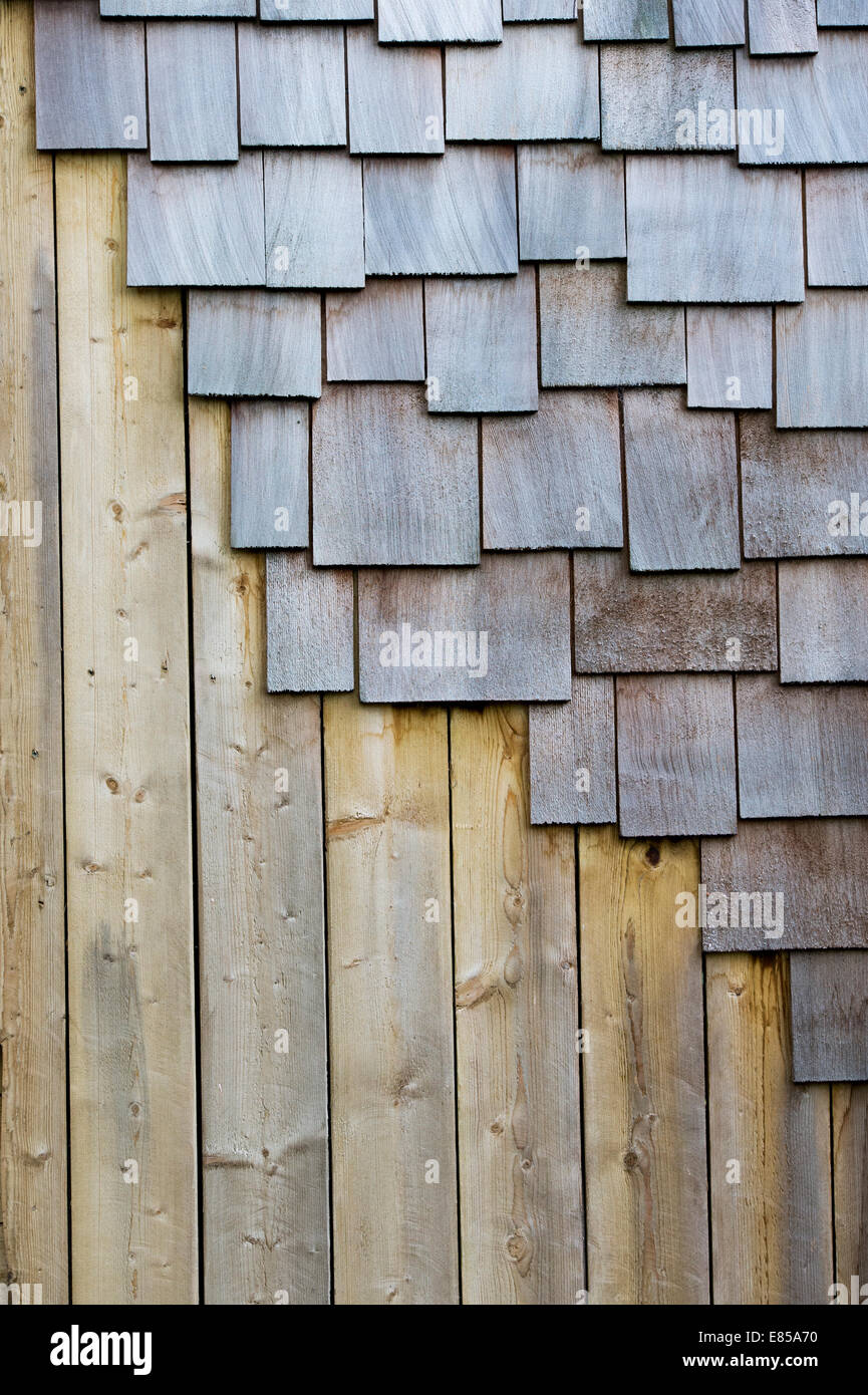 Roof shingles and planks of wood on the edge of a garden structure - Stock Image