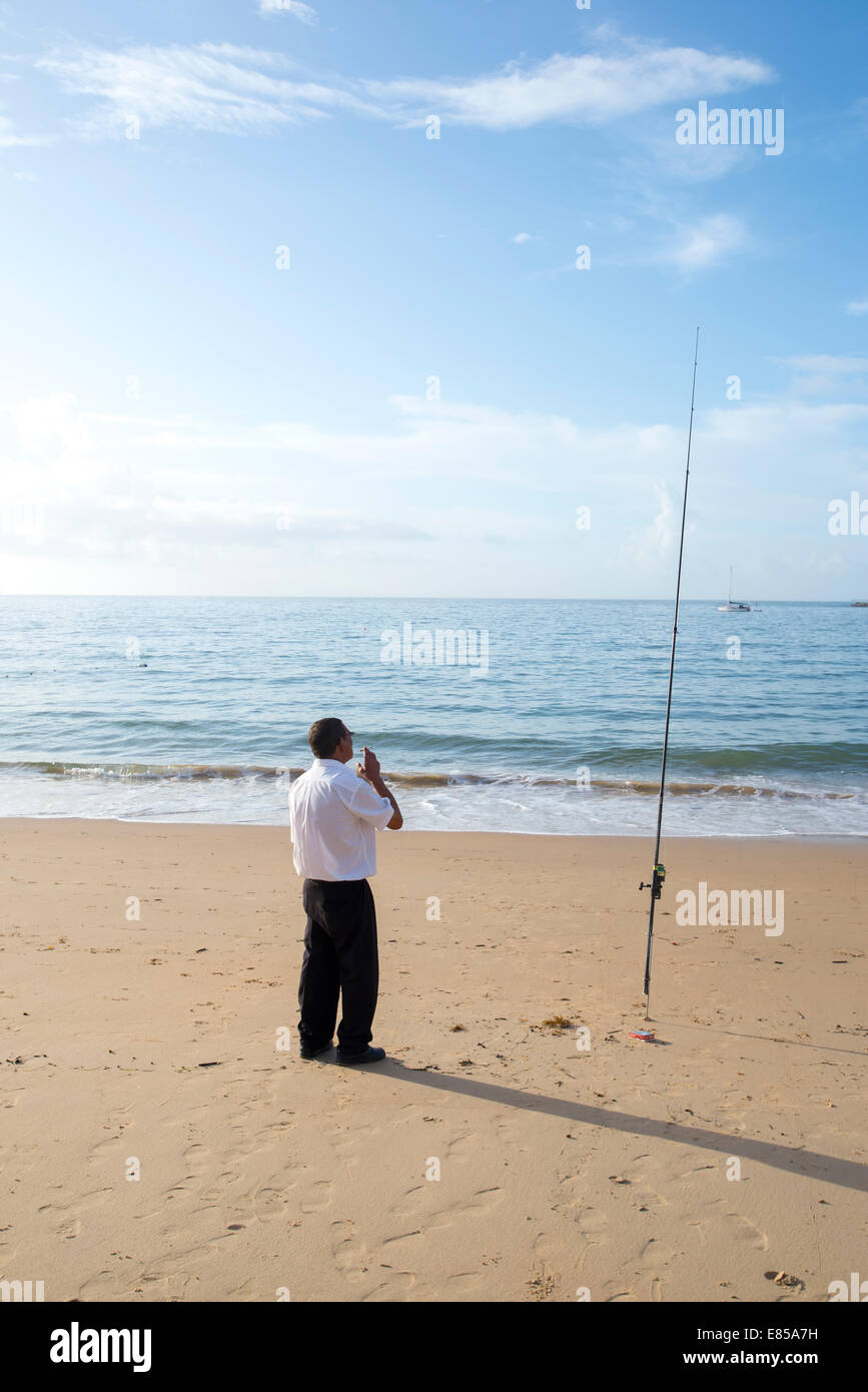 Man standing on cascais beach in black trousers and white shirt with fishing rod, meters away from the fish restaurant - Stock Image