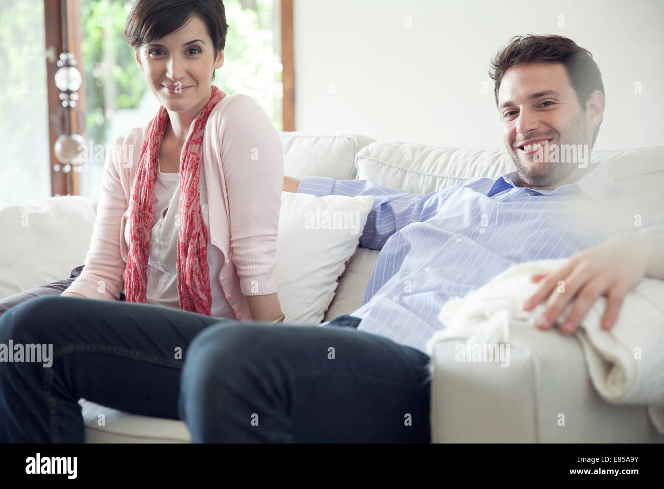 Couple relaxing on sofa at home - Stock Image