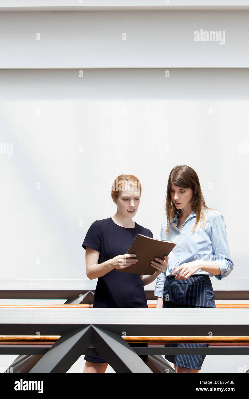 Businesswoman discussing file with colleague - Stock Image