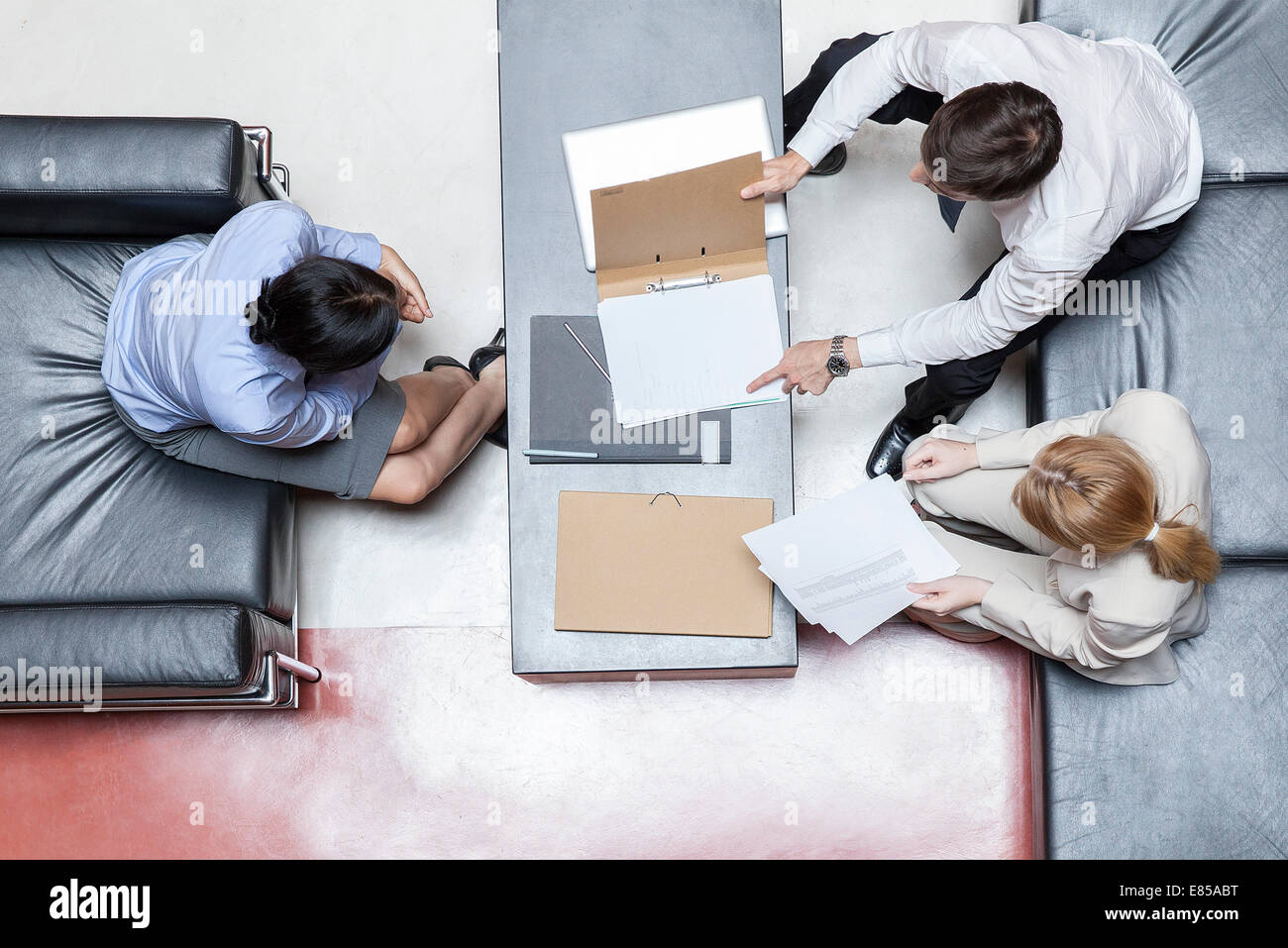 Executives in business meeting, overhead view - Stock Image