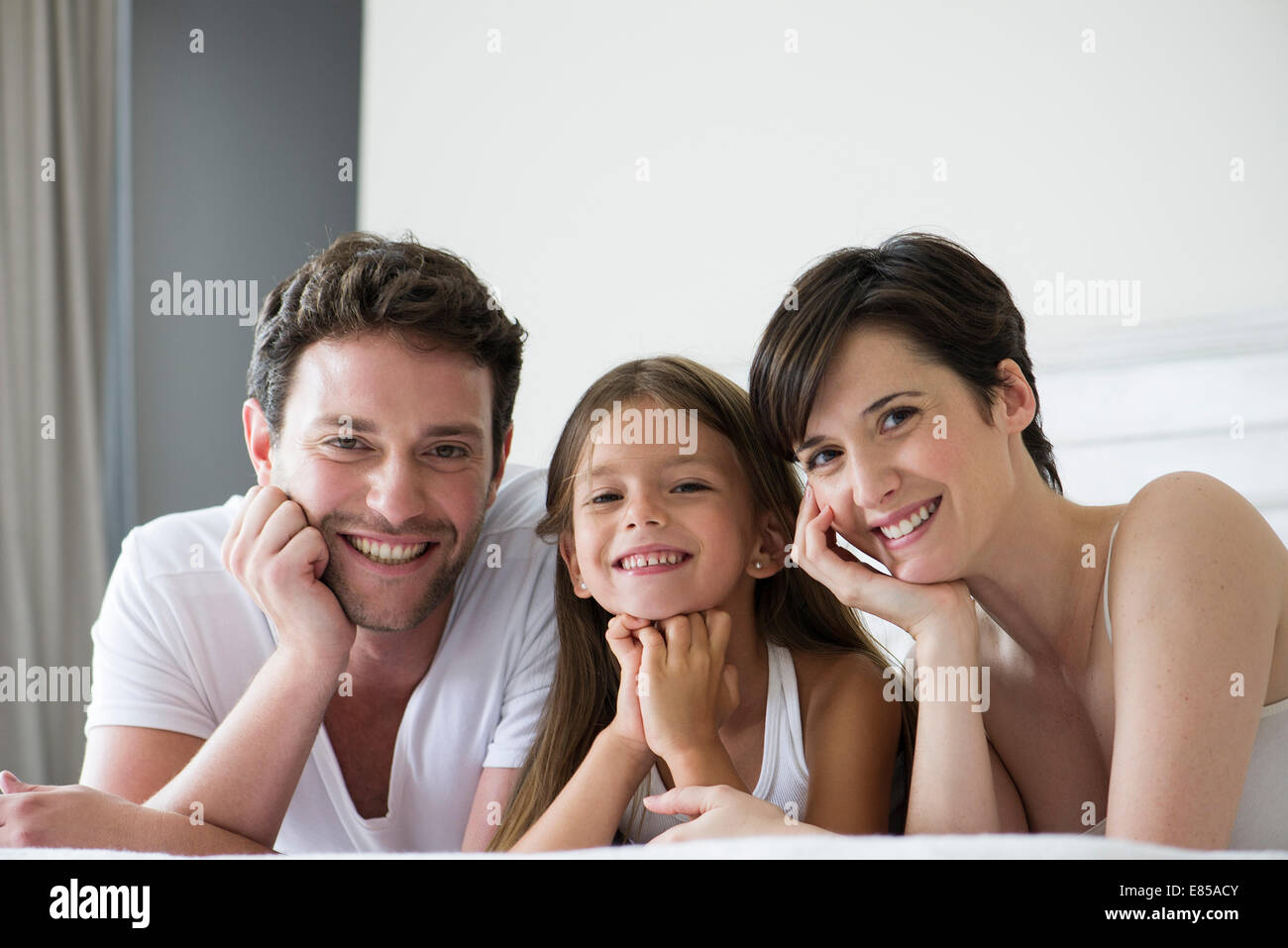 Parents and daughter lying on bed together, portrait - Stock Image